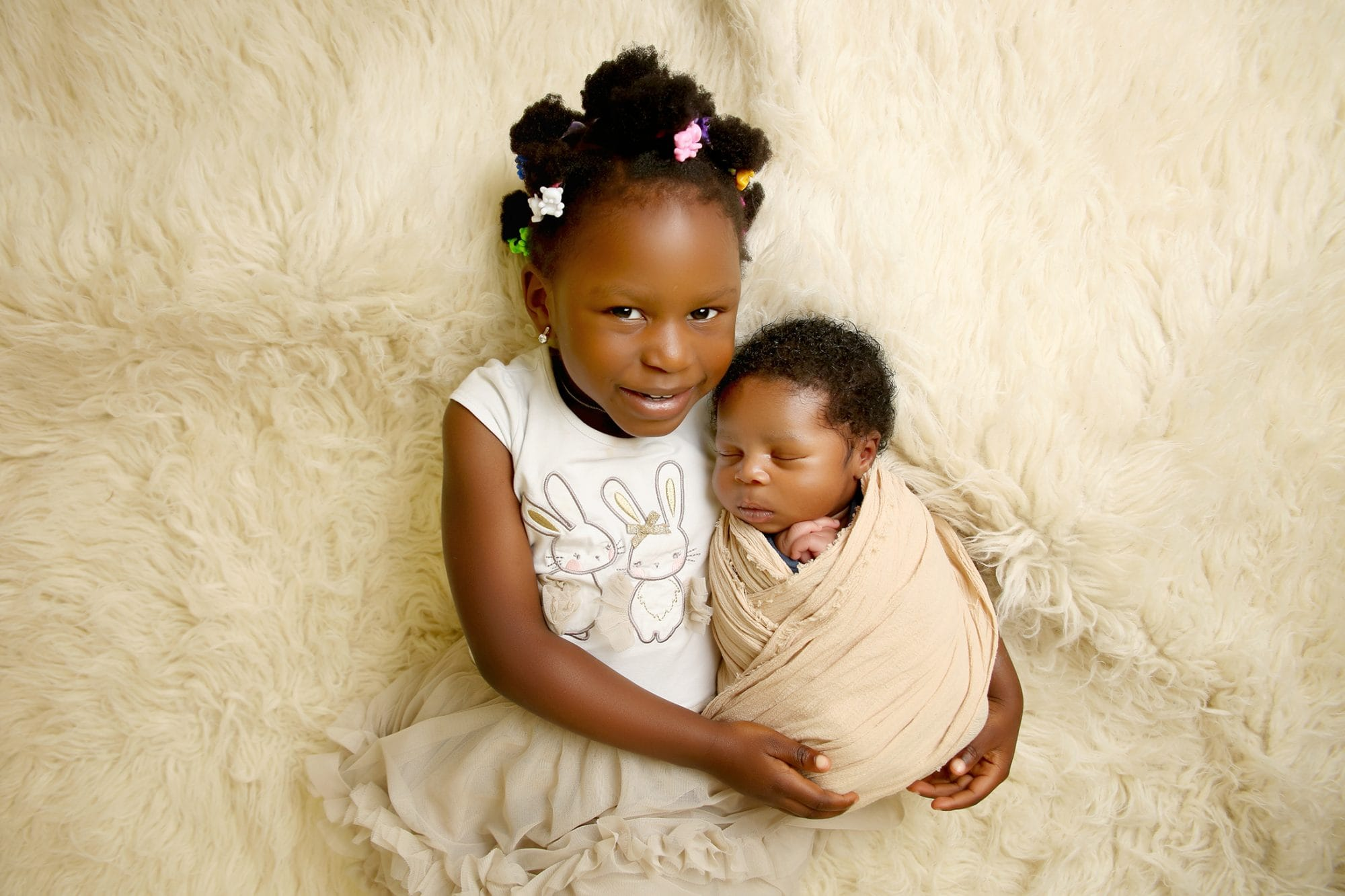 a nigerian girl laid down looking at the camera while holding her newborn baby brother who is wrapped up and asleep