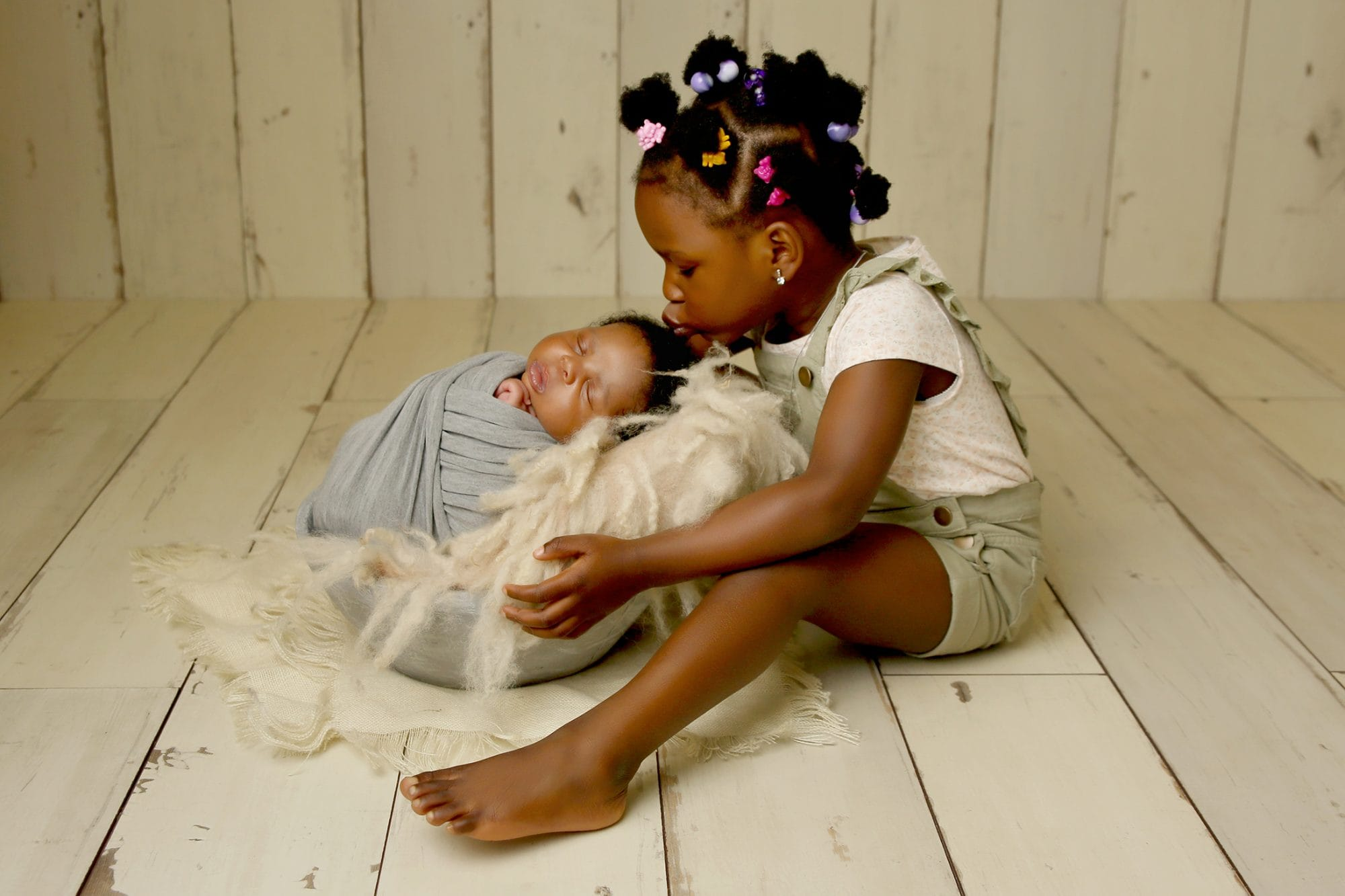 a nigerian girl sat kissing her newborn baby brother who is asleep in a grey bowl