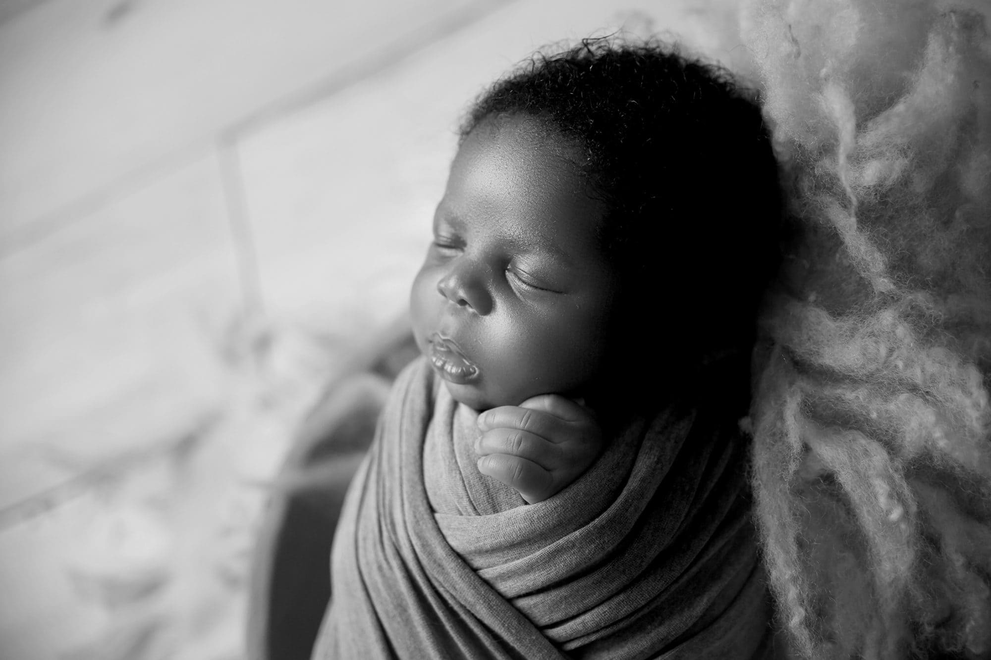 a close up black and white picture of a nigerian newborn baby boy asleep from the side