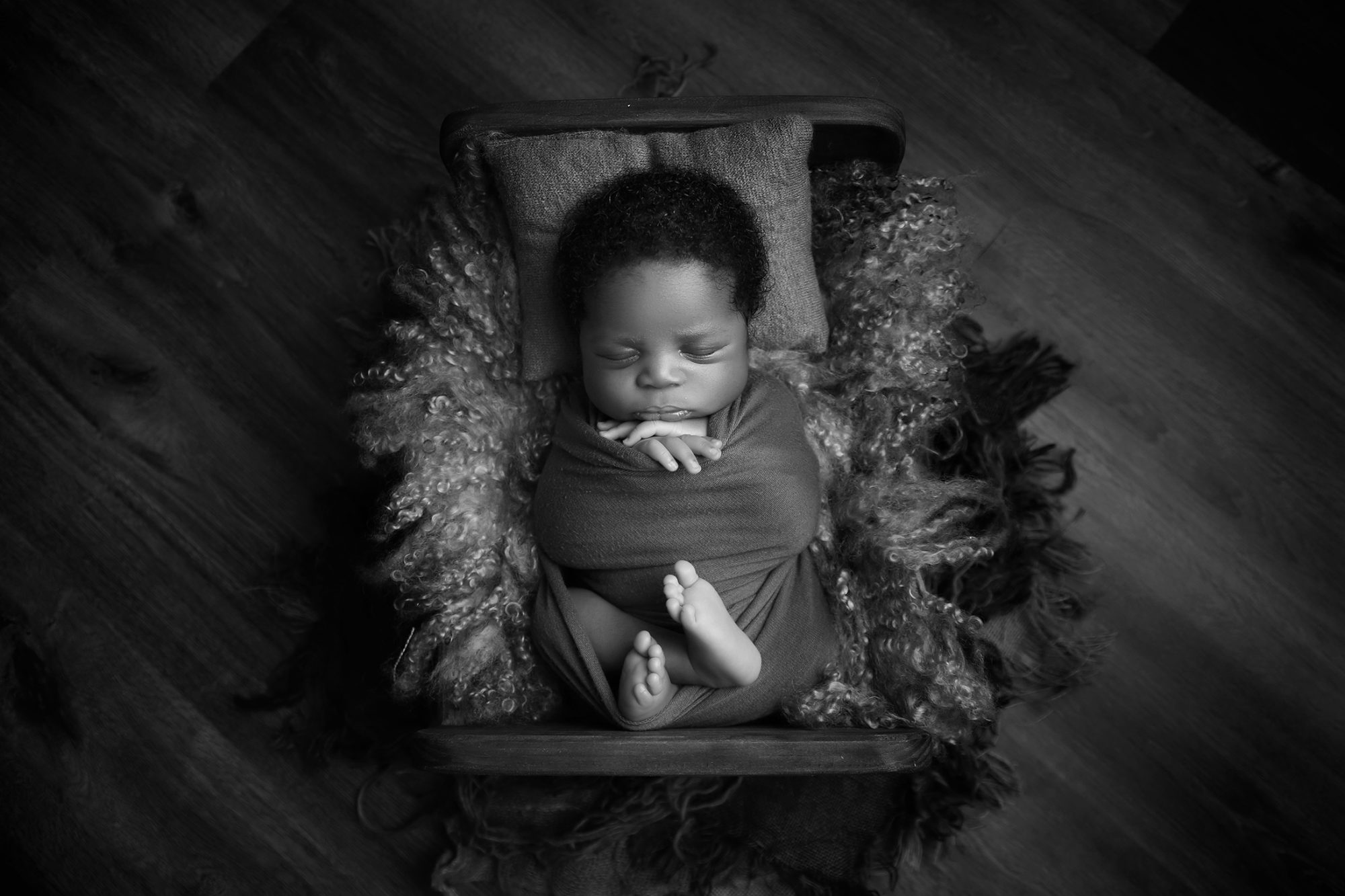 a black and white picture of a nigerian newborn baby boy asleep in a newborn bed