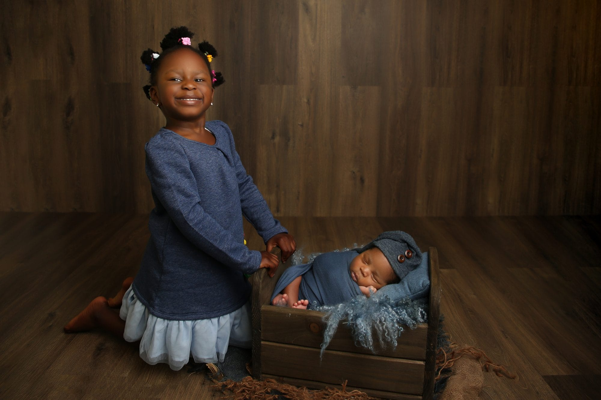 a nigerian girl on her knees holding onto a newborn bed with her newborn baby brother sleeping inside while looking at camera smiling