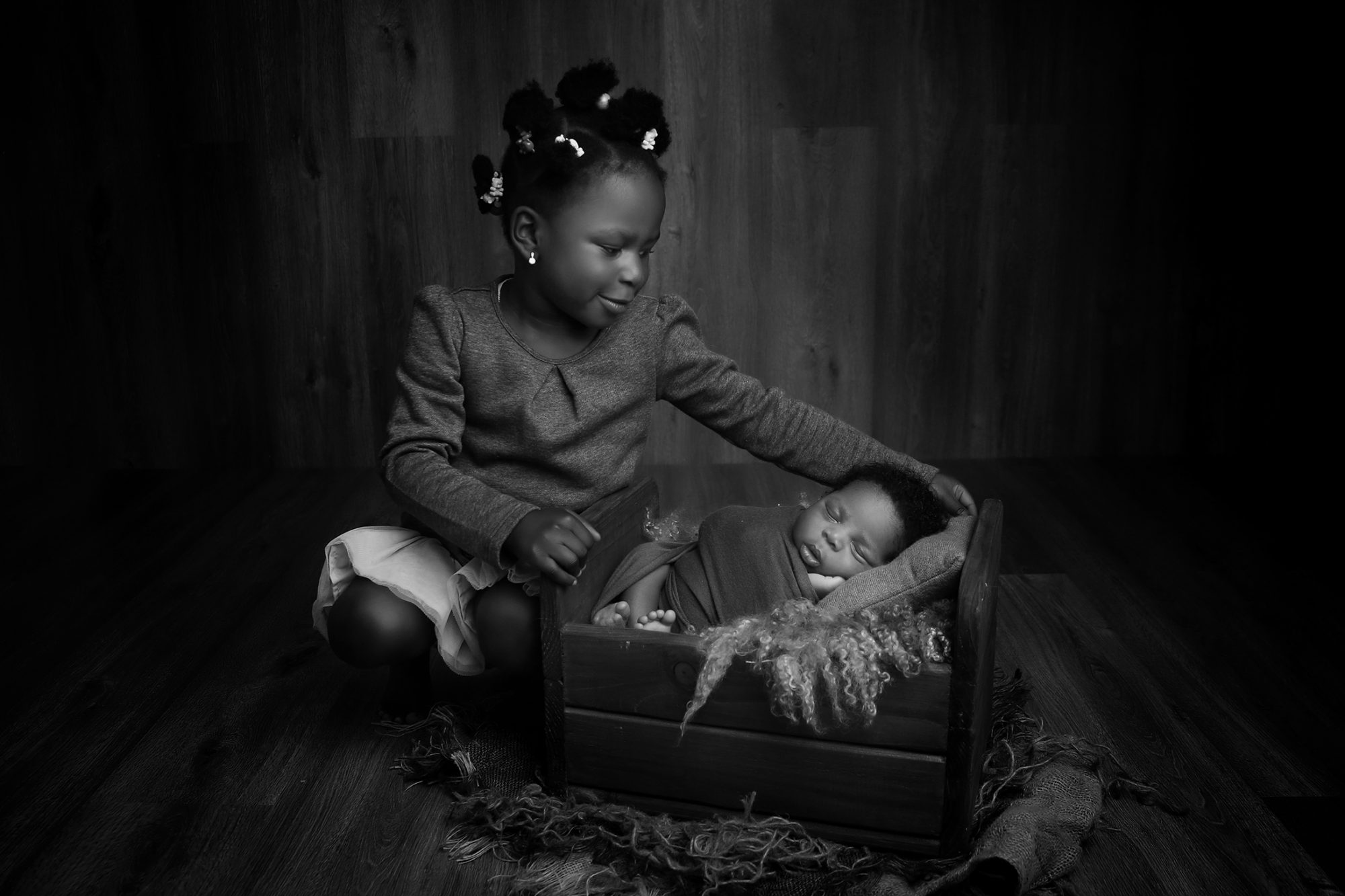 a nigerian girl sat holding onto a newborn bed while looking at her newborn baby brother