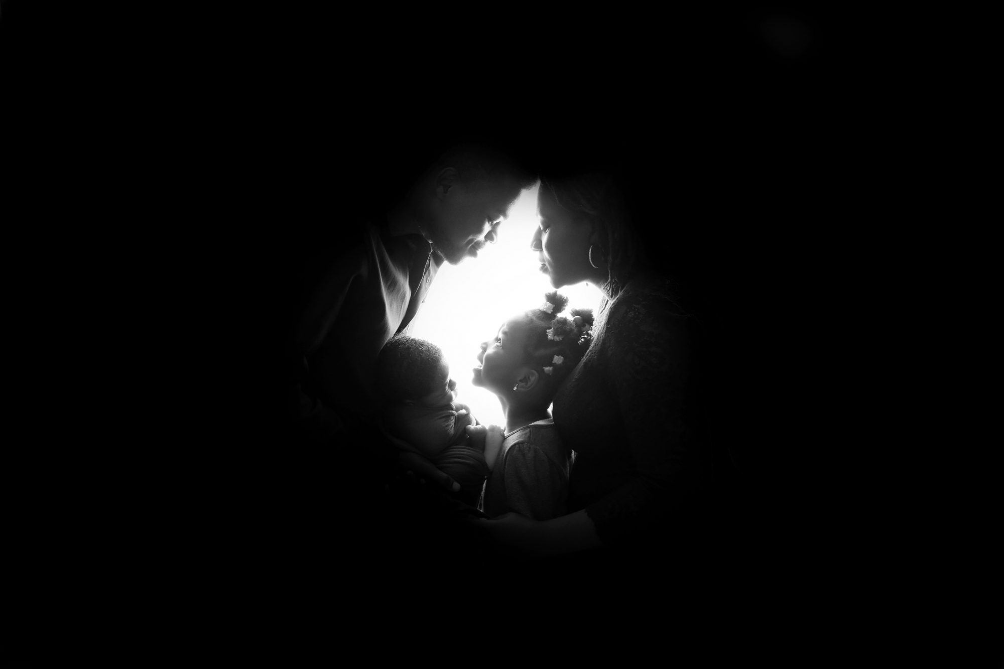 a silhouette of a nigerian mother, father, daughter and newborn baby boy