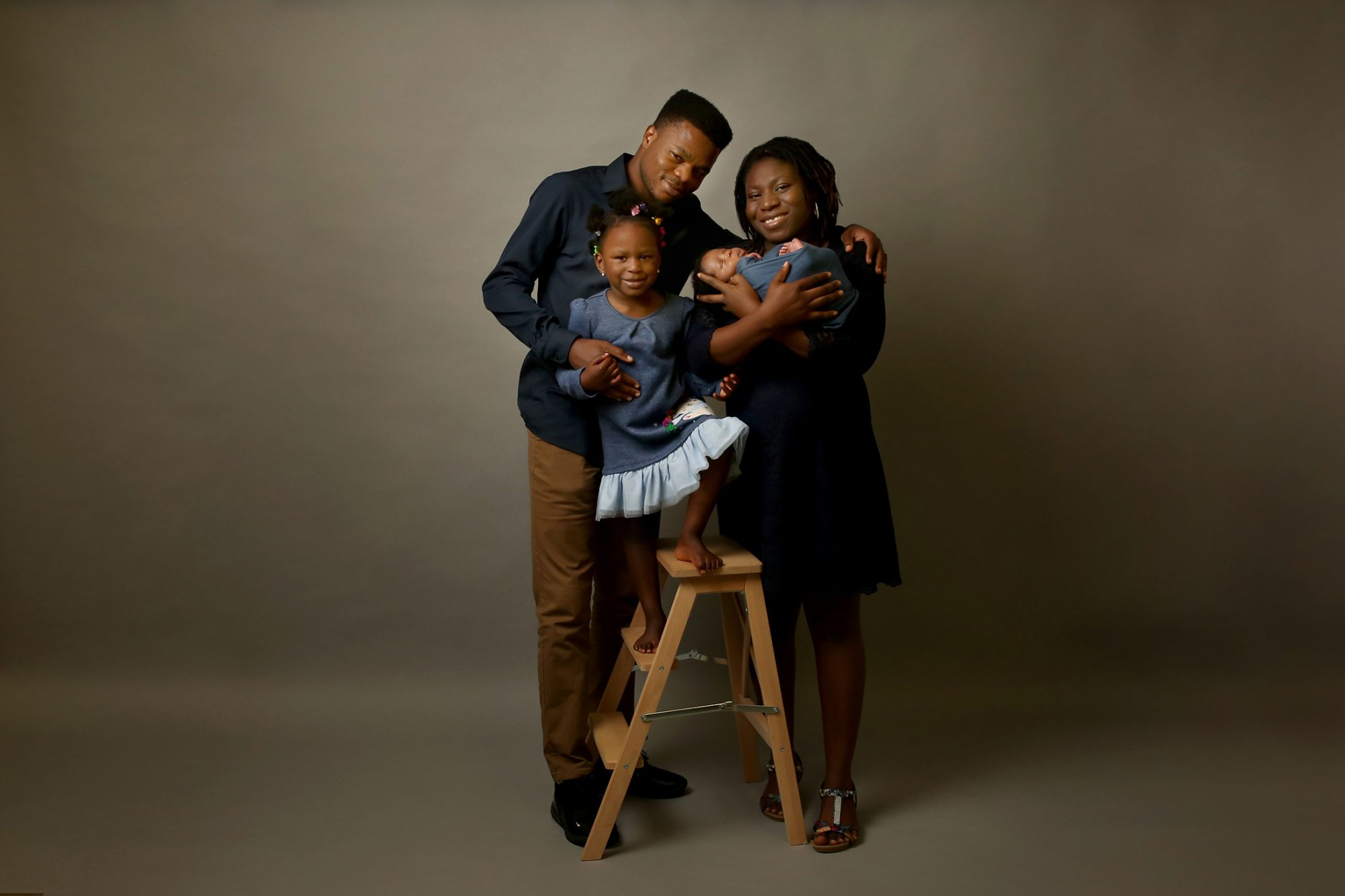 a nigerian mother holding a newborn baby boy and father holding daughter who is standing on wooden ladders