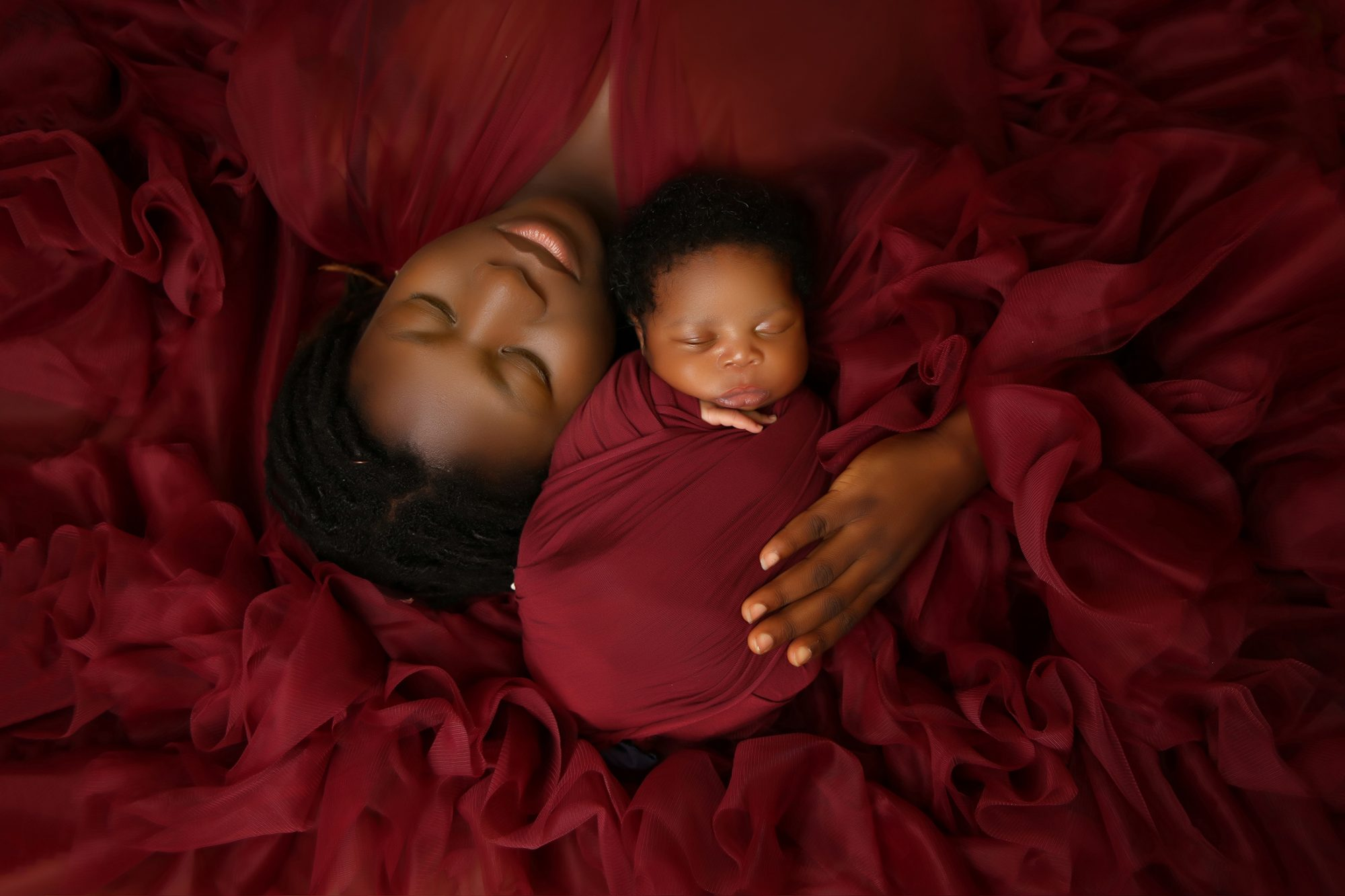 a nigerian mother upside down with eyes closed with hand on newborn baby boy in burgundy red chiffon