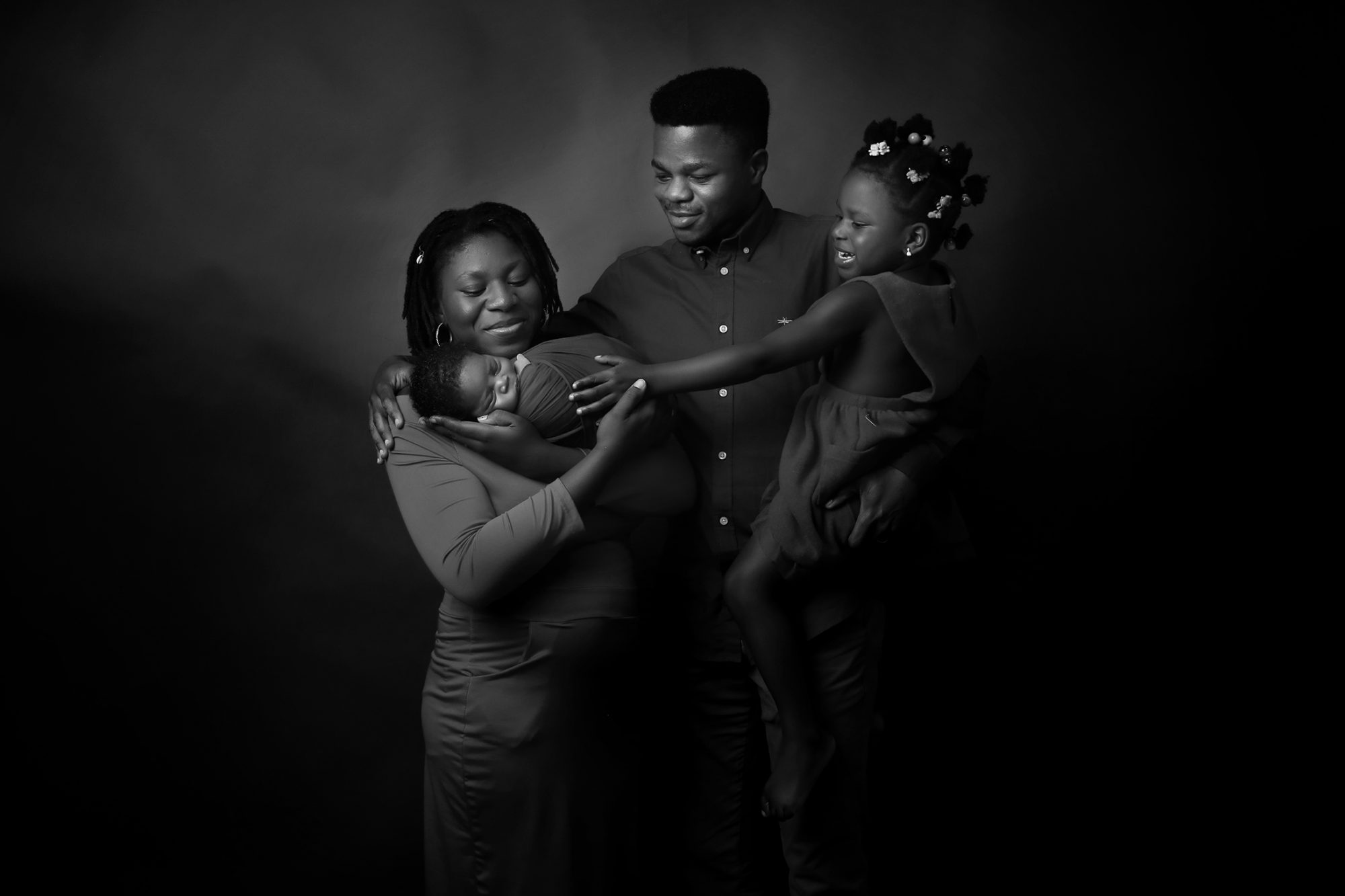 a beautiful nigerian mother, father and daughter smiling, looking and touching newborn baby boy