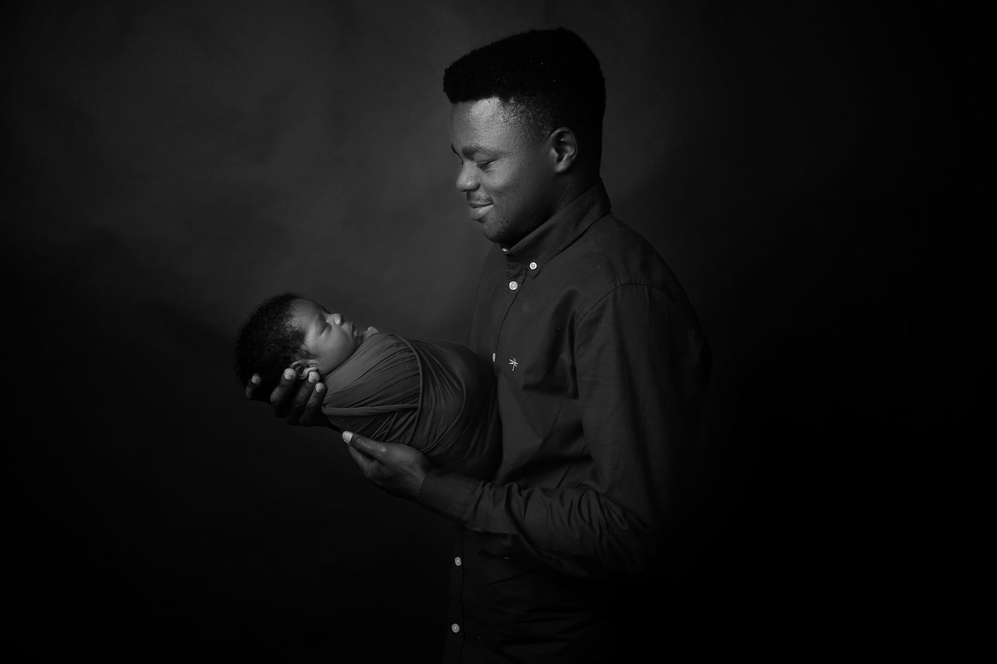 a nigerian father looking at a newborn baby boy while holding him in front of him
